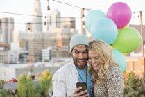 Пара, дивлячись на смартфон на даху партії, Лос-Анджелес, США — стокове фото