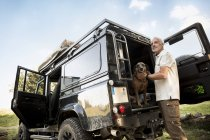 Senior man with dog at cross country vehicle — Stock Photo