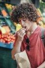 Jovem comendo cerejas na frente da banca de frutas de rua — Fotografia de Stock