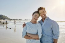 Portrait of smiling couple standing on beach — Stock Photo
