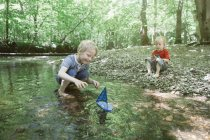 Two boys playing with a toy boat in a forest brook — Stock Photo