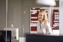 Lächelnde kaukasische Geschäftsfrau in modernem Büro — Stockfoto