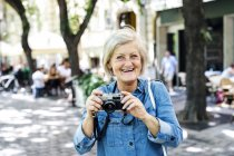 Cheerful senior adult woman holding camera outdoors — Stock Photo