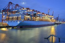 Industrial port of Hamburg with container ship and cranes illuminated in dusk, Germany — Stock Photo
