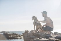 Junger Mann mit Hund am Strand — Stockfoto
