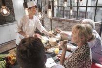 Glückliche Freunde und Koch gibt Essen Sampling im Kochkurs — Stockfoto