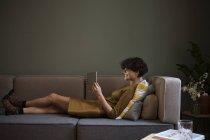 Jeune femme souriante utilisant une tablette sur le canapé à la maison — Photo de stock