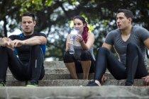 Amigos tomando un descanso en el parque de fitness, sentado en las escaleras - foto de stock