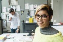 Porträt von lächelnden Architektin im Büro mit Kollegen auf Hintergrund — Stockfoto