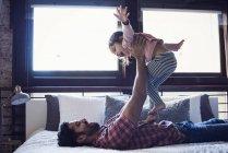 Pai brincando com a filha da criança deitada de volta no quarto — Fotografia de Stock