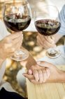 Close-up of senior couple hands with glasses of red wine and holding hands outdoors — Stock Photo
