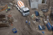 Concrete mixer on construction site and workers — Stock Photo
