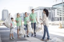 Group of volunteering children collecting garbage with litter sticks — Stock Photo