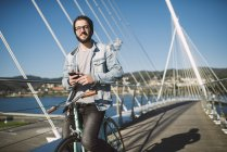 Casual young man with fixie bike on a bridge, Ferrol, Galicia, Spain — Stock Photo