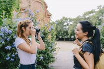 Mulher tirando foto de seu amigo — Fotografia de Stock