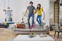 Retrato de pareja saltando en un sofá en una tienda de muebles - foto de stock