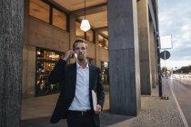 Porträt des Geschäftsmannes am Telefon am Abend zu Fuß in der Stadt — Stockfoto