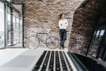 Businessman standing with bicycle in modern office — Stock Photo