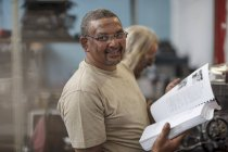 Portrait of smiling mechanic in workshop holding book — Stock Photo