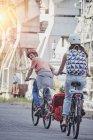 Задні портрет сім'ї, їзда на велосипеді з дочкою в причепі — стокове фото