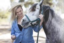 Smiling woman with horse on horse farm — Stock Photo