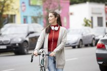 Woman with headphones and bicycle crossing street — Stock Photo