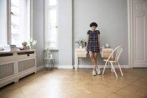 Щасливі молода жінка стоїть вдома і дивлячись на камеру — стокове фото