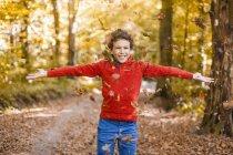 Menino sorridente jogando folhas no ar na floresta outonal — Fotografia de Stock