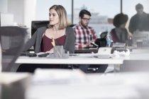 Женщины офисный работник работает на стол в среде занят — стоковое фото