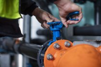Hands turning valve in factory — Stock Photo