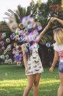 Freundinnen amüsieren sich mit Seifenblasen im Park — Stockfoto