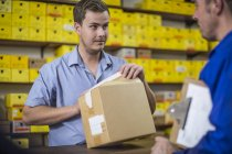Man in warehouse checking delivered cardboard box — Stock Photo