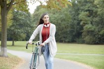 Woman with headphones and bicycle walking in autumnal park — Stock Photo