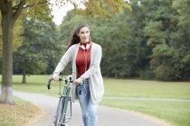 Женщина в наушниках и на велосипеде гуляет по осеннему парку — стоковое фото