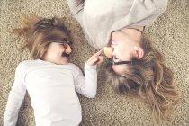 Madre e figlioletta sdraiati sul tappeto si divertono con gli occhiali comici — Foto stock