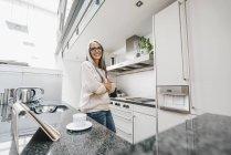 Donna sorridente con lunghi capelli grigi in cucina — Foto stock