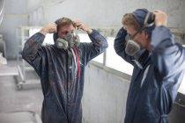 Factory worker in truck manufacture adjusting respirators — Stock Photo