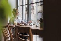 Молодая женщина с планшетом сидит в кафе и смотрит в окно — стоковое фото