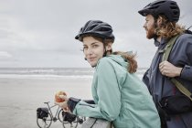 Couple on a bicycle trip having a break on jetty at the beach — Stock Photo