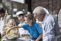Crianças ajuda chef na aula de culinária — Fotografia de Stock