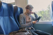 Jeune homme assis dans un train regardant tablette — Photo de stock