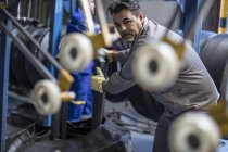Male tire repairman working in factory — Stock Photo