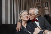 Uomo anziano baciare moglie sul divano — Foto stock