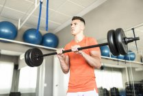 Man training triceps with bar at gym — Stock Photo
