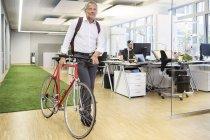 Businessman pushing bicycle — Stock Photo