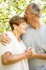 Старшая пара обнимается на свежем воздухе в зеленом саду — стоковое фото