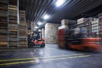 Чоловіки на навантажувача машини handeling складі ящиків розподілу заводі — стокове фото