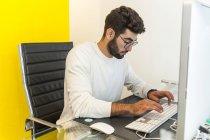 Jeune homme travaillant avec ordinateur dans un bureau moderne — Photo de stock