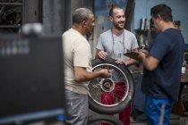 Механіка стоять разом в майстерні мотоцикл — стокове фото