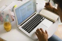 Adolescente haciendo deberes, vista parcial - foto de stock
